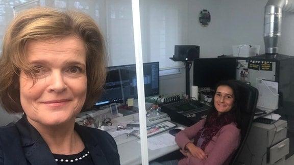 Bild zwei Frauen in einem Studio. Eine Frau sitzt vor einem Computer.