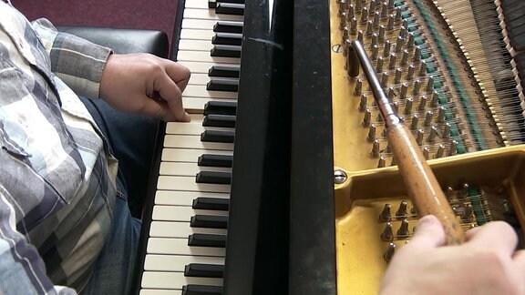 Ein Mann drückt mit einem Finger eine Taste auf einem Klavier.
