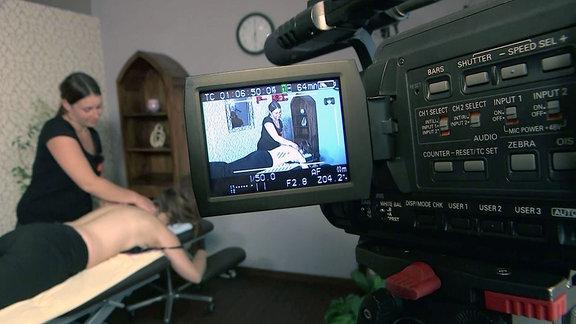 Eine Person wird auf einer Liege von einer Frau massiert. Eine Kamera nimmt die Szene auf und wir sehen diese Szene auch auf dem kleinen Bildschirm an der Kamera.