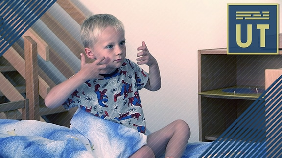 Teaserbild für den Beitrag über Gehörlose Kinder mit Untertiteln: Kleiner Junge sitzt auf dem Bett und gebärdet