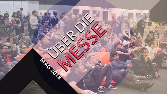 """Fans sitzend in der Messehalle; Schriftzug mit """"Über die Messe - MAG 2018"""""""