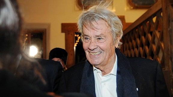 Alain Delon lächelt jemanden an.