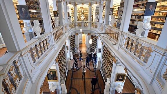 Besucher besichtigen den Rokokosaal der Herzogin Anna Amalia Bibliothek. Weitwinkel-Ansicht. Mittig am Geländer, viele Säule, weiß und gold dominieren, viele Bücher hinter den Säulen.