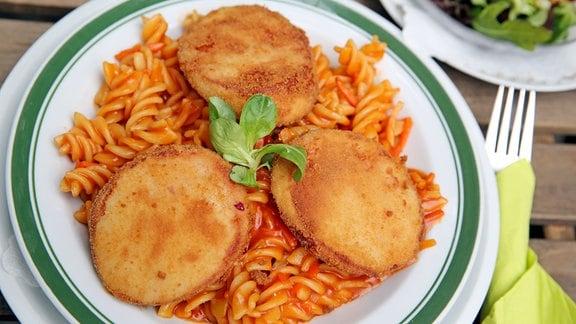 Drei panierte Scheiben Jagdwurst liegen als Jägerschnitzel auf einer Portion Spirelli mit Tomatensoße