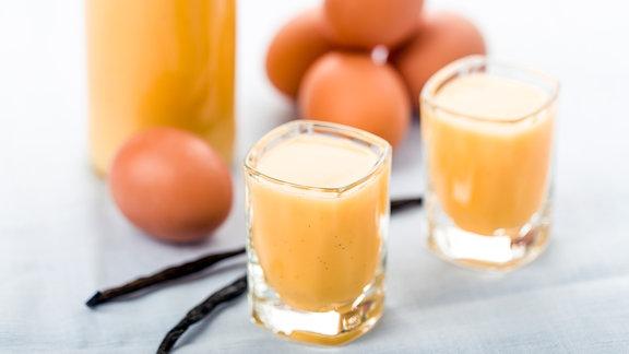 Eine Fasche und zwei Gläser mit Eierlikör, im Hintergrund liegen Eier
