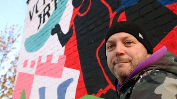 Alexander Lech vor einer Wand mit Graffiti