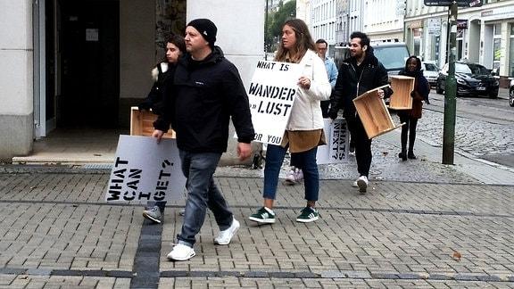 Eine Gruppe von Studierenden hält Plakate hoch und läuft durch die Stadt