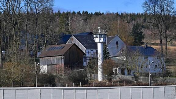 Die Mauer und ein Wachturm stehen mitten im Dorf