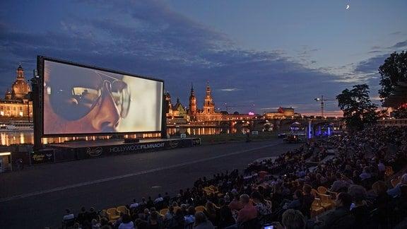Zahlreiche Gäste der «Filmnächte am Elbufer» sitzen vor der Kulisse der Dresdner Altstadt mit der Frauenkirche (l-r), dem Hausmannsturm, der Hofkirche und der Semperoper und schauen auf eine Kinoleinwand.