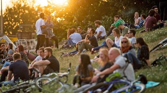 Zahlreiche Menschen sitzen 2018 kurz vor Sonnenuntergang am Königsufer in Dresden