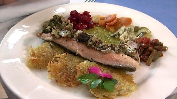 Ein gebratener Fisch liegt auf einem Teller