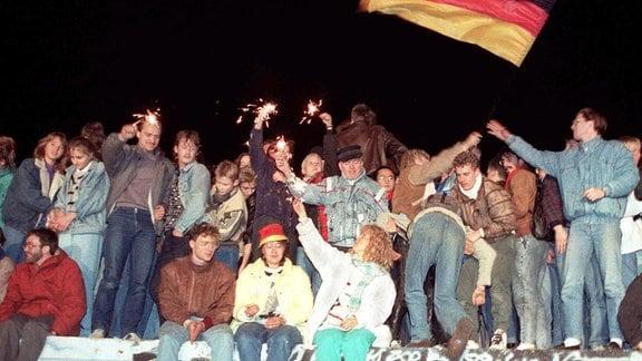Berlin, 10.11.1989 Mit Wunderkerzen in den Händen freuen sich die Menschen auf der Berliner Mauer über die Öffnung der deutsch-deutschen Grenzen.