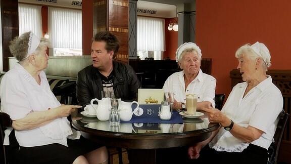 Ein Mann und drei ältere Damen sitzen an einem Tisch in einem Café