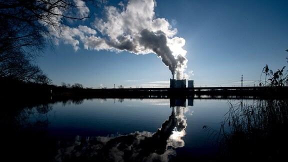 Die Silhouette des Kraftwerkes Schkopau zeichnet sich im Gegenlicht der Sonne ab.