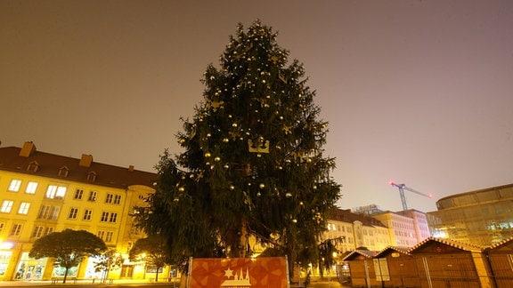 Magdeburg: Der Weihnachtsbaum steht geschmückt auf dem Alten Markt vor dem Rathaus, die Weihnachtsbuden stehen noch hinter einem Zaun.