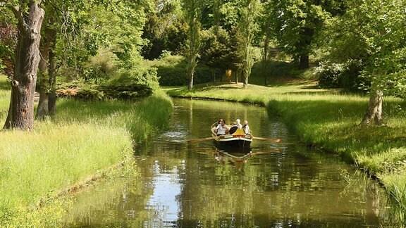 Eine Gondel fährt mit Besuchern auf den weit verzweigten Kanälen vor dem Gotischen Haus im Wörlitzer Park entlang