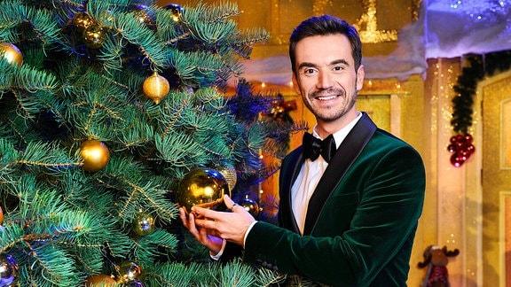 Florian Silbereisen steht neben einem Weihnachtsbaum, hält eine Kugel in der Hand und lächelt in die Kamera.