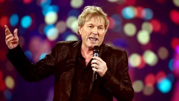 Bernhard Brink hält in der linken Hand ein Mikrofon und breitet seinen rechten Arm zu Seite aus.