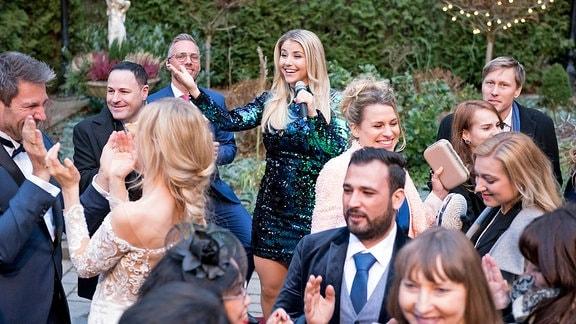 Christoph (Dieter Bach), Alicia (Larissa Marolt) und die Hochzeitsgäste genießen den Auftritt von Schlagerstar Beatrice Egli in vollen Zügen