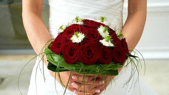 Eine Frau hält einen Brautstrauß in ihren Händen.