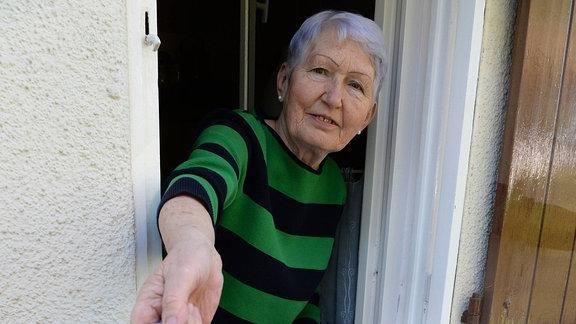 Ältere Frau nimmt Einkäufe am Fenster entgegen.