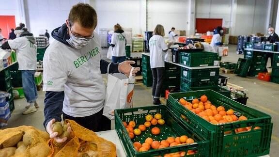 In einer Halle des Berliner Großmarkts packen ehrenamtliche Helfer der Berliner Tafel mit Atemschutzmasken Lebensmittel ein