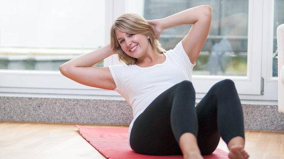 Eine Frau treibt Sport zu Hause