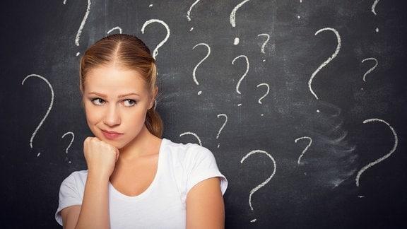 ein Mädchen steht überlegend vor einer Tafel mit vielen Fragezeichen