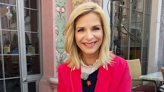Eine Frau mit blonden Haaren und roter Jacke sitzt in einem Straßencafe und ist etwas.