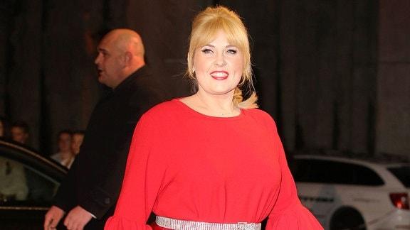 Maite Kelly ist rot gekleidet und läuft lächelnd über einen roten Teppich.