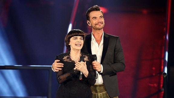 Moderator Florian Silbereisen in Lederhose mit Sängerin Mireille Mathieu