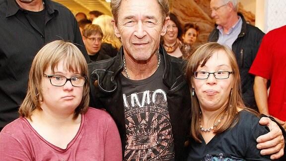 Musiker Peter Maffay lässt sich mit zwei Kindern ablichten, die am Down-Syndrom erkrankt sind.