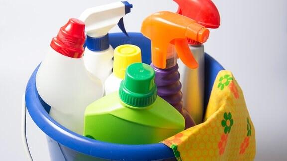 Eimer, Lappen und verschiedene Flaschen mit Reinigungsmitteln zum Putzen.
