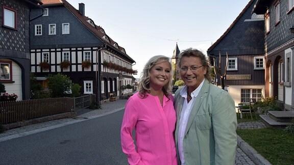 Kathrin und Peter stehen vor einem Hotel.