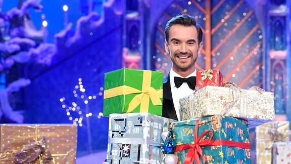Florian Silbereisen hält Geschenkpakete in der Hand.