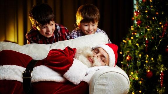 Zwei Kinder betrachten einen schlafenden Weihnachtsmann.