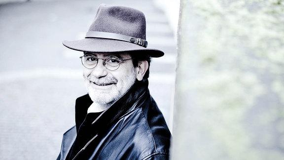 Dirigent Andrea Marcon lächelnd mit Hut auf der Straße