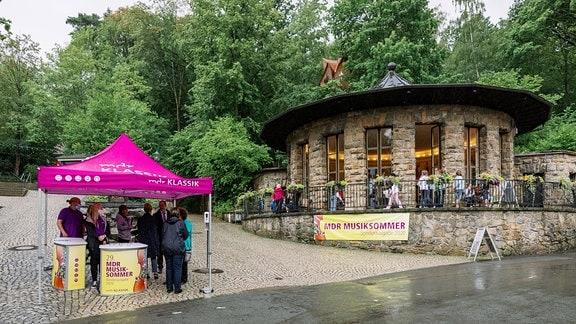 Rundes Steinhaus im Grünen, Zugang zu den Saalfelder Feengrotten, daneben der Infostand des MDR-Musiksommers