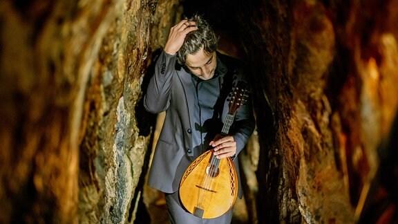 Mandolinist Avi Avital in einem engen Gang der Saafelder Feengrotten