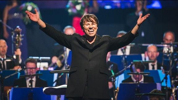 Kristjan Järvi reißt Arme zum Schluss-Applaus nach oben und lacht ausgelassen