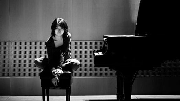 Pianistin Claire Huangci sitzt auf der Klavierbank neben einem Flügel