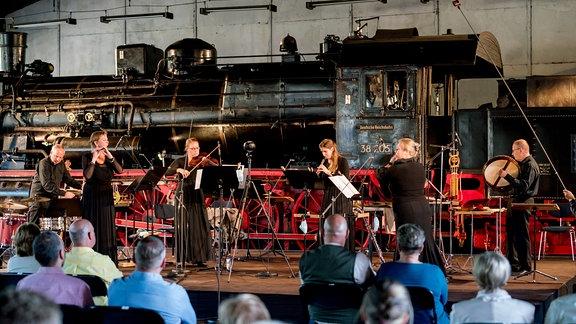 Musikerinnen und Musiker vor einer Lokomotive bei der MDR-Musiksommer Sonderausgabe im Eisenbahnmuseum Chemnitz