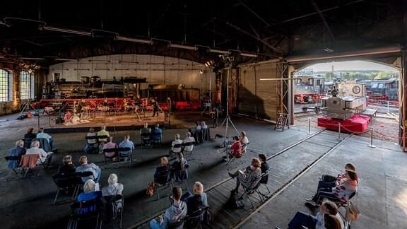 Blick in eine Halle des Eisenbahnmuseums Chemnitz, wo Musiker vor Publikum ein Konzert im Rahmen MDR-Musiksommer Sonderausgabe spielen
