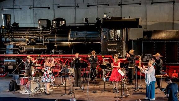Musikerinnen und Musiker bei der MDR-Musiksommer Sonderausgabe vor einer Lokomotive im Eisenbahnmuseum Chemnitz