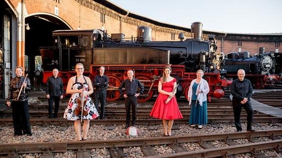 Festlich gekleidete Musikerinnen und Musiker bei der MDR-Musiksommer Sonderausgabe vor Lokomotiven im Eisenbahnmuseum Chemnitz