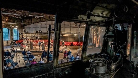 Blick aus einem Lokomotiv-Fenster auf Bühne und Publikum bei der MDR-Musiksommer Sonderausgabe im Eisenbahnmuseum Chemnitz