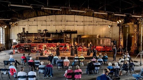 Musikerinnen und Musiker auf der Bühne bei der MDR-Musiksommer Sonderausgabe im Eisenbahnmuseum Chemnitz. Im Hintergrund eine Lok, im Vordergrund das Publikum.
