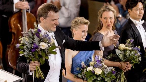 Risto Joost mit Blumenstrauß in der Hand auf der Bühne bei der Eröffnung des MDR-Musiksommers in Görlitz