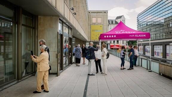 Vor dem Eingang des Kultur- und Kongresszentrums Gera stehen Menschen um ein lilafarbenes MDR KLASSIK-Zelt.