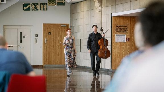 Der Cellist Daniel Müller-Schott und die Cembalistin Irina Zahharenkova laufen vor ihrem Konzert bei der MDR-Musiksommer Sonderausgabe am 26. Juli 2020 durch das Foyer des Kultur- und Kongresszentrums Gera.